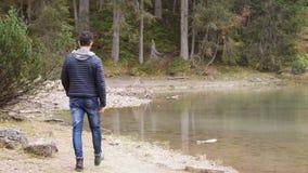 Jonge mens die in weelderig groen berglandschap wandelen stock video