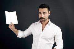Jonge mens die in wit overhemd een boekje lezen stock foto's