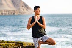 Jonge mens die yoga doen en in het op zee strand van de boompositie mediteren royalty-vrije stock afbeelding