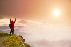 Jonge mens die zich bovenop berg bevinden Stock Foto