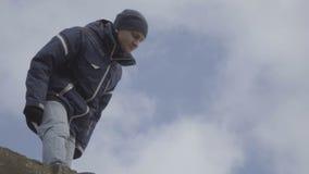 Jonge mens die zich bovenop een van de berghemel langzame motie bevinden als achtergrond stock video