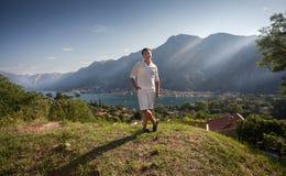 Jonge mens die zich bovenop hoge berg bij zonnige dag bevinden Stock Foto's