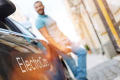 Jonge mens die zich dichtbij zijn nieuwe elektrische auto bevinden royalty-vrije stock afbeeldingen