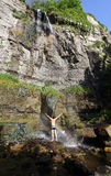 Jonge mens die zich onder waterval met regenboog bevindt Stock Fotografie
