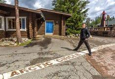 Jonge mens die zich op de lijn van de noordpoolcirkel in Rovaniemi bevinden stock foto's