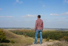Jonge mens die zich op een heuvel bevinden die van landschap genieten Concept reis en vrijheid stock afbeelding