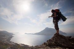 Jonge mens die zich op een rots bevindt Royalty-vrije Stock Foto's