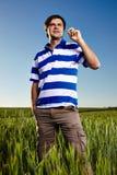 Jonge mens die zich op een tarwegebied bevinden Royalty-vrije Stock Foto's