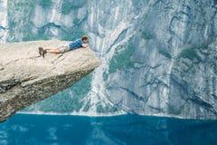 Jonge mens die zich op rots in de bergen van Noorwegen bevinden Sleeplijntong royalty-vrije stock afbeeldingen