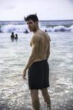 Jonge mens die zich op strand door de oceaan bevinden royalty-vrije stock afbeelding