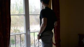 Jonge mens die zich tegen venster bevinden, droevig of ongerust gemaakt, het denken stock videobeelden