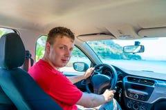 Jonge mens die zijn auto drijven Stock Afbeeldingen
