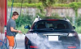 Jonge Mens die Zijn Auto schoonmaken stock foto