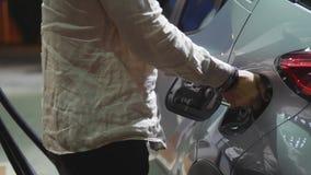 Jonge mens die zijn auto van brandstof voorzien bij benzinestation stock foto