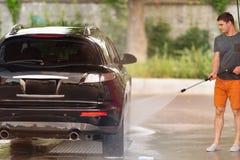 Jonge mens die zijn auto wassen bij de autowasserette stock afbeelding