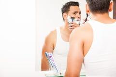 Jonge mens die zijn baard met een scheermes scheren stock foto