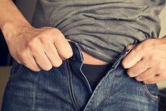 Jonge mens die zijn broeken proberen vast te maken Stock Foto's