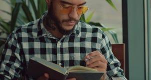 Jonge mens die zijn creatief idee schrijven of toekomstige dagen plannen in notitieboekje stock video