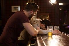 Jonge mens die zijn dronken vriend helpen royalty-vrije stock fotografie