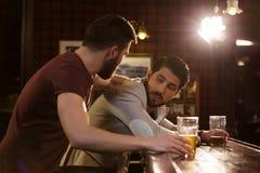 Jonge mens die zijn dronken vriend helpen stock afbeelding