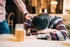Jonge mens die zijn dronken vriendenslaap op lijst wekken bij bar of bar royalty-vrije stock fotografie