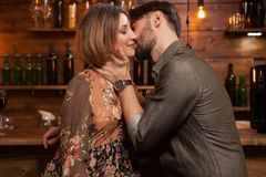 Jonge mens die zijn fiance op een nacht uit in een uitstekende bar kussen royalty-vrije stock foto's