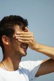 Jonge mens die zijn gezicht behandelt Stock Afbeelding