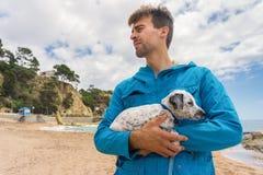 Jonge mens die zijn goedgekeurd gemengd Dalmatisch puppy in toneelplaats met strand, hemel en overzees op achtergrond houden Het  royalty-vrije stock foto's