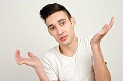 Jonge mens die zijn handen opheffen die… benieuwd zijn Stock Fotografie