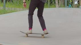 Jonge mens die zijn het met een skateboard rijden vaardigheden in een skatepark opleiden stock video