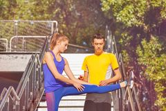 Jonge mens die zijn meisjesvriend het uitrekken zich benen helpen Stock Afbeeldingen