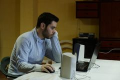 Jonge mens die zijn mobiel, tablet, laptop en hoofdtelefoons met behulp van stock foto