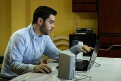 Jonge mens die zijn mobiel, tablet, laptop en hoofdtelefoons met behulp van royalty-vrije stock afbeeldingen