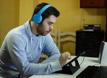 Jonge mens die zijn mobiel, tablet, laptop en hoofdtelefoons met behulp van stock afbeeldingen