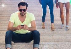 Jonge mens die zijn mobiele telefoon in de straat met behulp van Royalty-vrije Stock Afbeelding