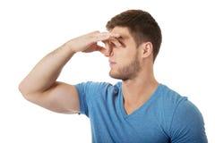 Jonge mens die zijn neus knijpen stock foto's