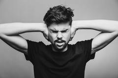 Jonge mens die zijn orenhanden behandelen Stock Fotografie