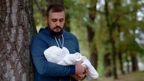 Jonge mens die zijn pasgeboren dochter op zijn handen houden stock footage