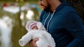 Jonge mens die zijn pasgeboren dochter op zijn handen houden stock videobeelden