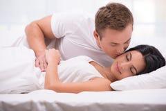 Jonge mens die zijn slaapvrouw kussen stock afbeeldingen