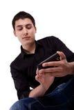 Jonge mens die zijn slimme telefoon bekijkt. Stock Afbeeldingen