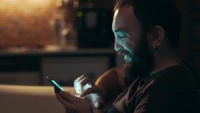 Jonge mens die zijn slimme telefoon in dark met behulp van stock videobeelden