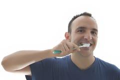Jonge mens die zijn tanden borstelt stock afbeelding