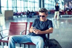 Jonge mens die zijn telefoon controleren terwijl het wachten van zijn vlucht in de lucht royalty-vrije stock afbeelding
