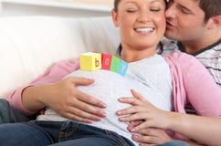 Jonge mens die zijn zwangere vrouw kust Stock Afbeelding