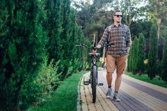 Jonge Mens die in Zonnebril met Fiets op de Zomerpark lopen Royalty-vrije Stock Afbeeldingen