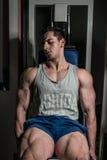Jonge mens die zwaargewicht oefening voor benen op de uitbreidingen van het machinebeen doen stock afbeelding
