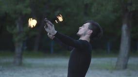 Jonge mens die in zwarte kleren een show met vlam uitvoeren die zich op riverbank bevinden Het bekwame fireshowkunstenaar uitadem stock footage