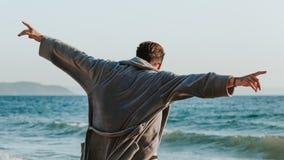 Jonge mens in een badjas op het strand stock afbeeldingen