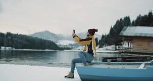 Jonge mens in een geel jasje en een rode hoed die beelden nemen tussen haakjes zit hij op een blauwe boot in het midden van stock videobeelden